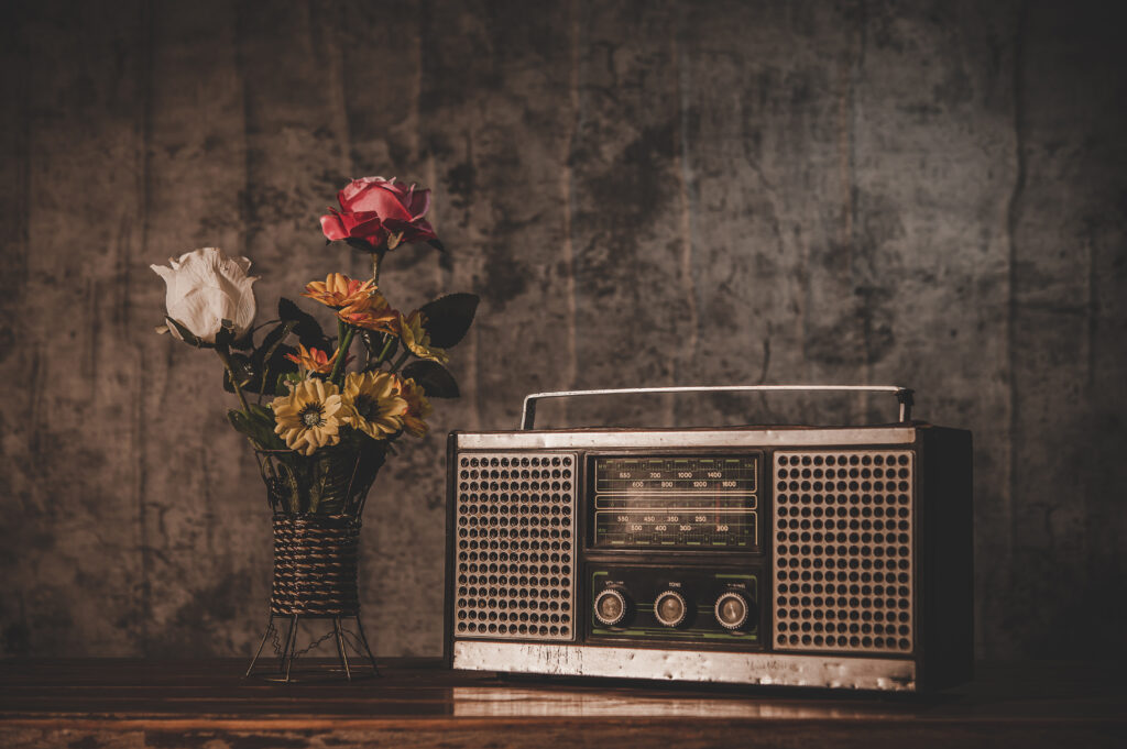 Still life with a retro radio receiver and flower vases.
